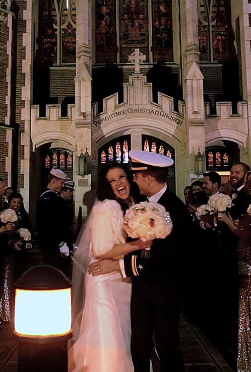 laughing bride and groom after military sword arch